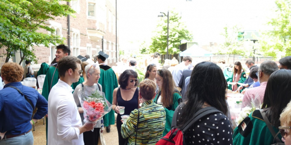 students and faculty mingle in the courtyard outside Seigle Hall